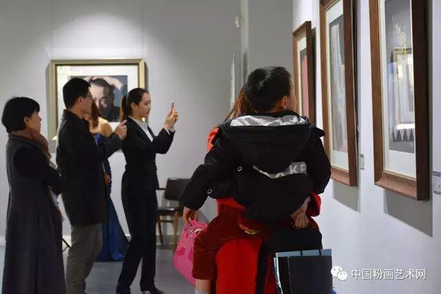 Visitantes viendo y fotografiando los cuadros de M Dolores GIl